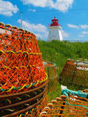 Lobster pots and lighthouse — Stock Photo