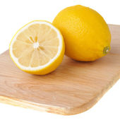 One and a half of lemon on chopping board — Stock Photo