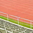 Red running track and  stadium seats. — Stock Photo