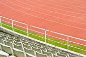 Red running track and stadium seats. — Стоковое фото