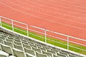 Red running track and stadium seats. — Stock Photo