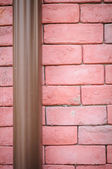 Red brick wall with pipe — Stock Photo