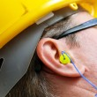 Yellow earplug into the ear close up — Stockfoto
