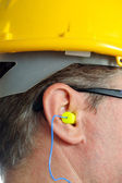 Yellow earplug into the ear — Stock Photo