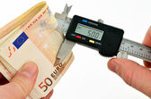 Measuring euro banknotes with vernier caliper — Stock Photo