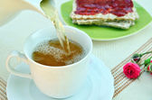 Pouring tea in cup with crispy bread and jelly — Stock Photo