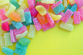 Colorful jelly candies isolated on yellow — Stock Photo