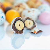 Candy with peanuts covered with multicolored glaze on a white ba — Stock Photo