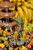 Chocolate fountain with fruit skewers — Stock Photo