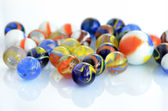 A handful of colorful glass marbles on a white background. — Stock Photo