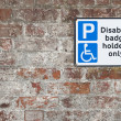 Disabled parking space plate on brick wall — Stock Photo