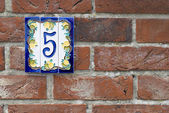 Brick wall with house number plate — Stock Photo