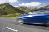 Blue car speeding, Lake District, UK — Stock Photo