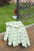 Green garden gloves on bench — Stock Photo