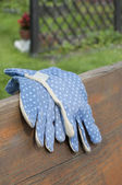Garden gloves on bench — Stock Photo