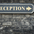 Stock Photo: Receptions arrow sign on brick wall
