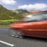 Speeding red car, Lake District, UK — Stock Photo #13531412