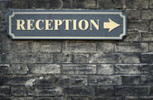 Receptions arrow sign on brick wall — Stock Photo
