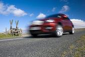 Red car speeding on empty mountain road — Stock Photo