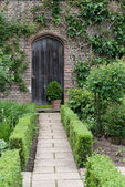 Secret garden. English garden path and door — Stock Photo