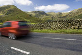 Speeding red car, Lake District, UK 2 — Stock Photo
