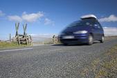 Blue MPV speeding on mountain road — Stock Photo