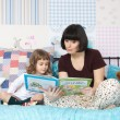 Mom reading a book to her little daughter — Stock Photo