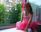 Sad little girl sitting near the window — Stock Photo