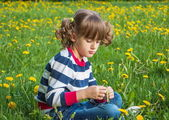 Child portrait on the background of dandelions — Stock Photo
