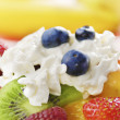 Sweet tasty fruit salad in the bowl with whipped cream — Stock Photo