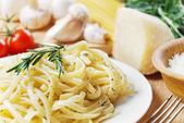 Pasta in the white plate on the wooden table — Foto Stock