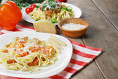 Pasta with shrimps and sauce on the wooden table — Photo