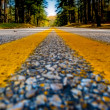 Close up of yellow lines on road — Stock Photo