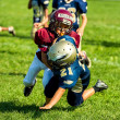 Stock Photo: Youth football player tackles another