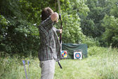 Bowman on shooting ranch with a bow and arrows — Stock Photo