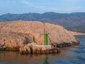 Skalnaté pobřeží a zelený maják — Stock fotografie