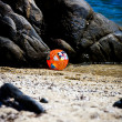 A beachball next to the rock on a summer holiday in Sarti, Greec - Stock Photo