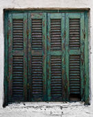Achient wooden turquoise window on a white house in Sarti, Greec — Stock Photo