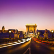 The lit of the Szechenyi Chain Bridge is a suspension bridge that spans the River Danube of the beautiful, decorative Budapest, the capital city of Hungary at night — Stock Photo