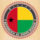 Carte d'epoca etichetta della bandiera della Guinea-Bissau. — Vettoriale Stock