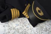 Captain uniform and navigation chart — Stock Photo