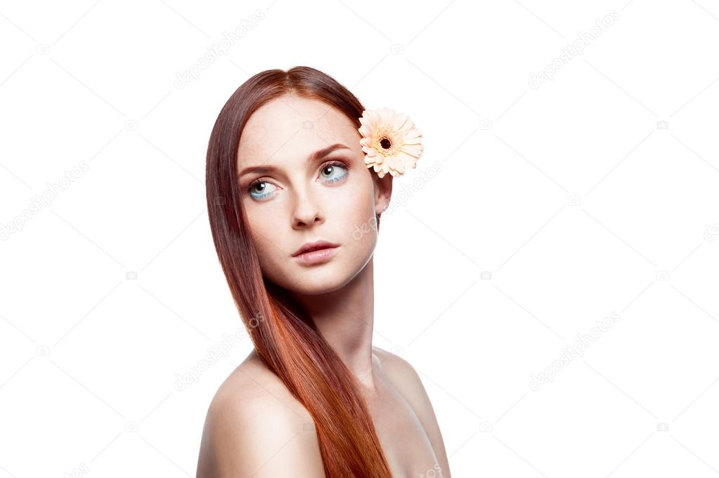 Portrait of young red-haired green-eyed female with flower in hair  Stock Photo #13385292