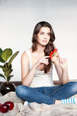 Thoughtful young casual female with red flower — Stock fotografie