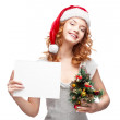 Young casual girl in santa hat holding sign — Stock Photo