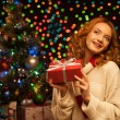 Young smiling woman holding red christmas gift — Stock Photo #13808868