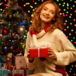 Young smiling woman holding red christmas gift — Stock Photo #13808874