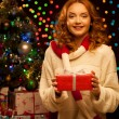 Young smiling woman holding red christmas gift — Stock Photo #13808879