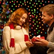 Young happy smiling casual couple making a present — Stock Photo
