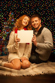 Young happy smiling casual couple holding sign — Stock Photo