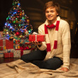 Young smiling man holding red christmas gift — Stock Photo #13928619
